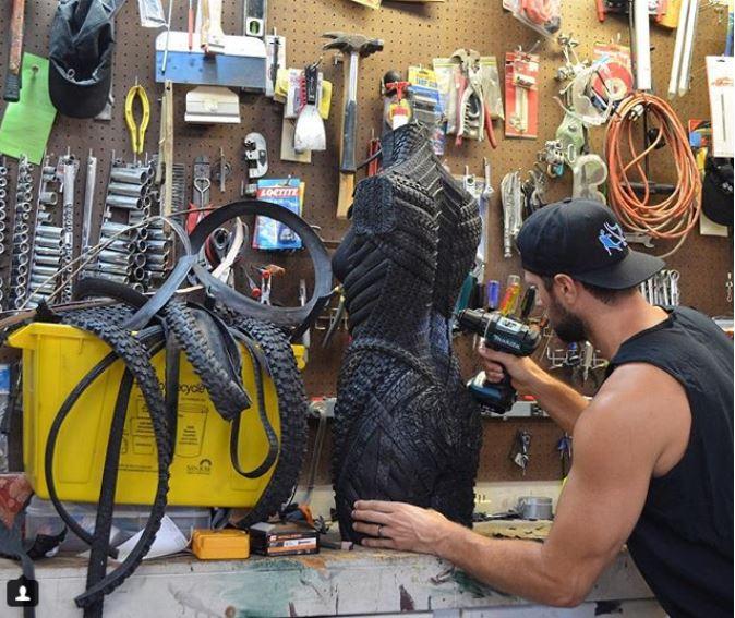 El escultor Blake McFarland trabajando en una de sus piezas hecha con neumáticos