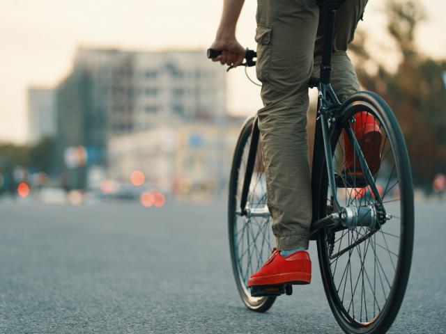 Primer plano de las piernas de un hombre en bicicleta clásica por las calles de una ciudad