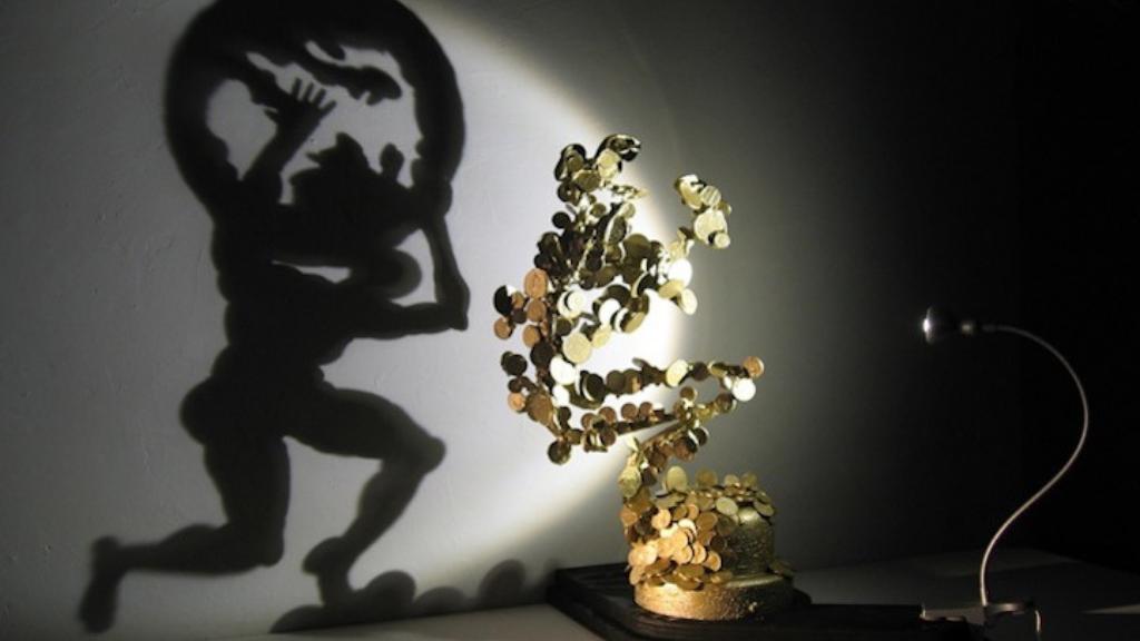 Atlas llevando el peso del mundo sobre sus hombros obra de Diet Wiegman creada con la sombra de un grupo de monedas