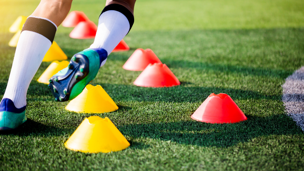 Jugador de fútbol entrenando en un campo de césped artificial con relleno de caucho reciclado