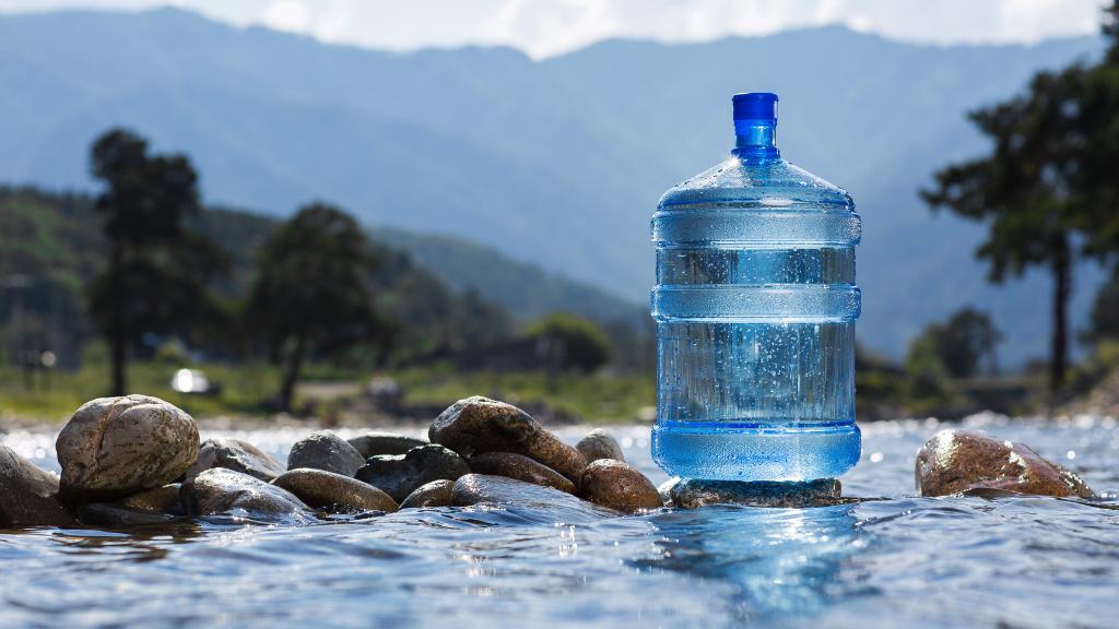Garrafa de agua con material reciclado sobre un manantial