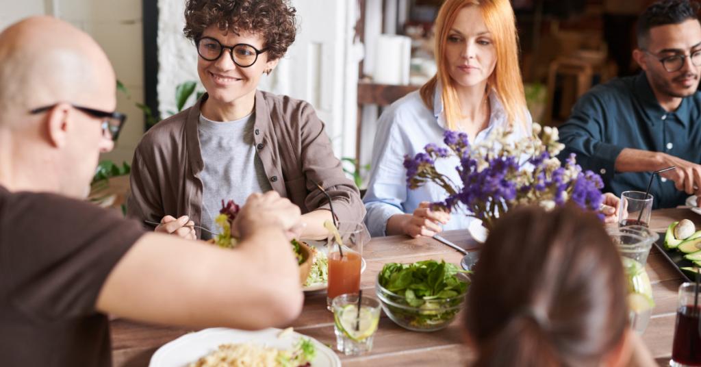 Varias personas comiendo alrededor de una mesa