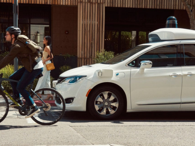 Coche autónomo de Waymo circulando por una calle con un ciclista al lado